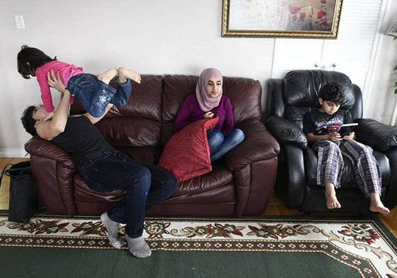 Fifteen-year-old Bilal Al Rasoul tosses his youngest sister, Sava, 3, while sitting with Marwa, 13, and Mohammad, 12, at the family's Thorncliffe Park home last month.