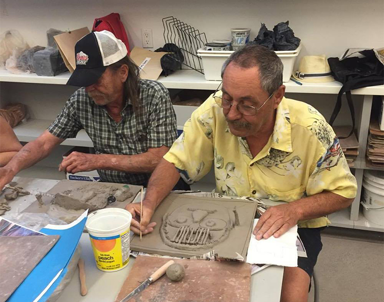 People working with clay to make art