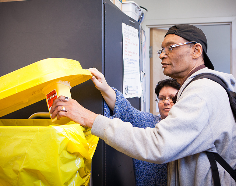 Man being assisted with placing object in a yellow bin