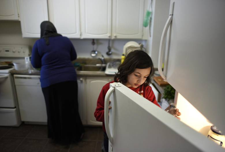 Rama Al Dibel, 9, grabs something from the fridge while helping her mom, Abir Abdel Al Kader, prepare a meal.