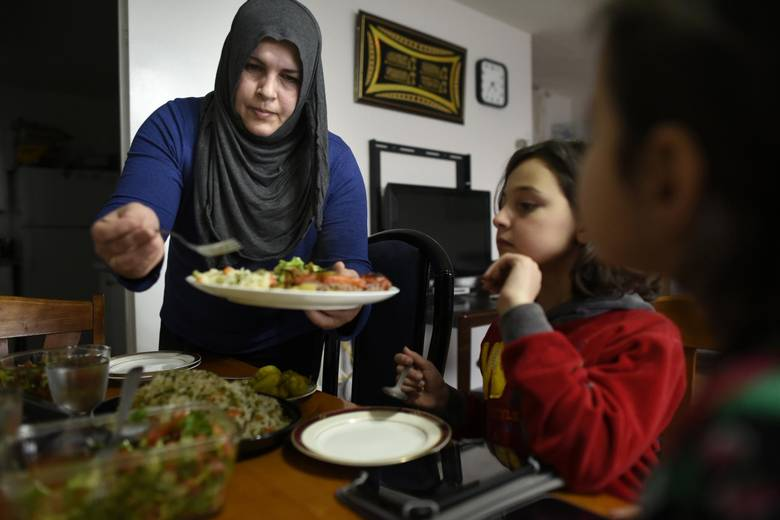 Abir Abdel Al Kader serves a late afternoon meal for her daughters Rama Al Dibel, 9, (C) and Rimas Al Dibel, 6.