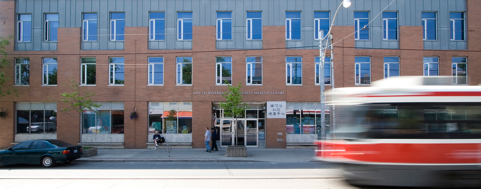The South Riverdale Community Health Centre building with a streetcar passing by