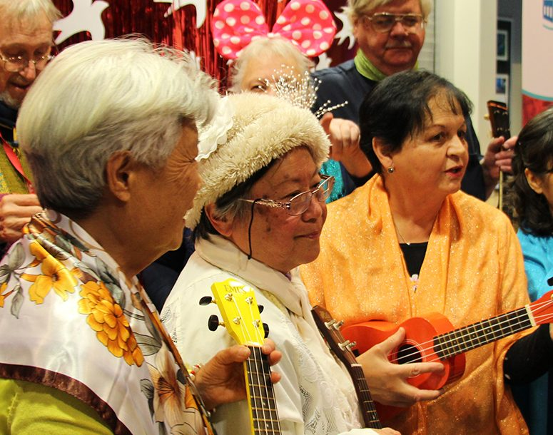 Seniors at SRCHC playing music with ukeleles and singing during the 40 year anniversary event