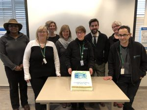 Group of people celebrate with a cake