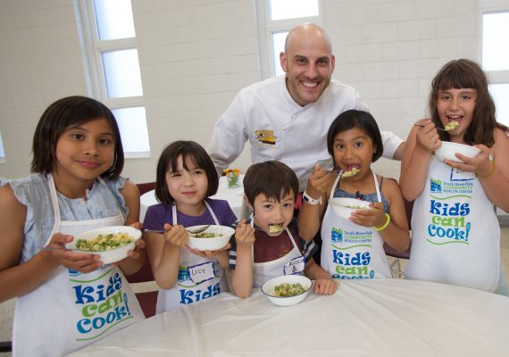 Chef Afrim with children ages 8 to 10 in the Kids Can Cook program.
